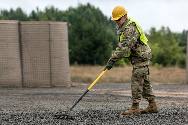 Pfc. Travis Kearns, a signal support system specialist in the West Virginia Army National Guard, assigned to 812th Engineer Company, 1092nd Engineer Battalion, 111th Engineer Brigade, based out of Eleanor, West Virginia, uses a rake to level out the recently placed gravel while at Drawsko Pomorskie Training Area, Poland, during Resolute Castle, July 12, 2018. Resolute Castle is a multinational training exercise for NATO and U.S. Army engineers, which supports Atlantic Resolve by promoting interoperability. Atlantic Resolve is a demonstration of the United States' commitment to the collective security of Europe through the deployment of rotational U.S. forces in cooperation with NATO ally and partner nations. (U.S. Army photo by Spc. Dustin Biven / 22nd Mobile Public Affairs Detachment)