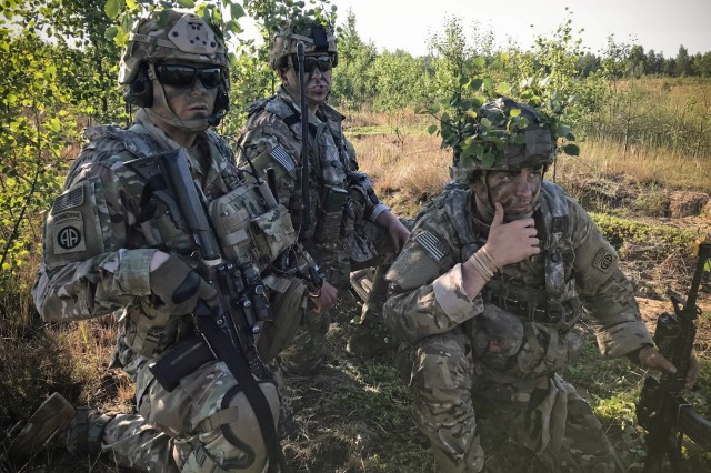 Command Sgt. Maj. Christopher C. Goodart (left) and other Paratroopers of the 82nd Airborne Division observe potential mock enemy activity on June 9, 2018 near Rukla, Lithuania during Swift Response 18, a multinational training exercise designed to maintain readiness and cohesiveness of participating units from several countries. These Soldiers are assigned to 5th Squadron, 73rd Cavalry Regiment, 3rd Brigade Combat Team, 82nd Airborne Division.  The 82nd Airborne Division began the mission at its home station of Fort Bragg, N.C., conducting a non-stop transcontinental flight that featured a mid-air refueling.  The exercise is scheduled for run June 7-15. (U.S. Army photo by 1st Sgt. Andrew Kosterman/22nd Mobile Public Affairs Detachment)