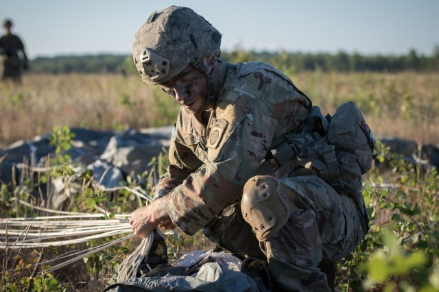 Spc. Sean Shelts, a paratrooper assigned to the U.S. Army's 1st Battalion, 508th Infantry Regiment, 3rd Brigade Combat Team, 82nd Airborne Division, packs his parachute and collects his gear after jumping from an aircraft near Rukla, Lithuania, as part of Swift Response 18 June 9, 2018. Swift Response 18 is a multinational training exercise designed to maintain readiness and cohesiveness of participating units from several countries. The 82nd Airborne Division began the mission at its home station of Fort Bragg, N.C., conducting a non-stop transcontinental flight that featured a mid-air refueling. The exercise is scheduled to run June 7-15. (U.S. Army photo by Spc. Andrew McNeil / 22nd Mobile Public Affairs Detachment)