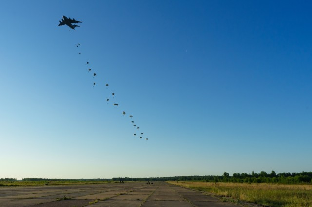 U.S. Army paratroopers with the 3rd Brigade Combat Team, 82nd Airborne Division, jump from a U.S. Air Force C-17 Globemaster III as part of Swift Response 18 at a training area near Rukla, Lithuania, June 9, 2018. Swift Response 18 is a multinational training exercise designed to maintain readiness and cohesiveness of participating units from several countries. Soldiers of the 3rd BCT started the training mission at their home station of Fort Bragg, N.C. and conducted a non-stop transcontinental flight that featured a mid-air refuel to conduct the jump into Lithuania. (U.S. Army photo by Sgt. Gregory T. Summers / 22nd Mobile Public Affairs Detachment)