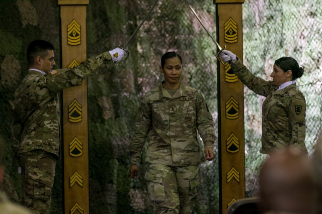 Sgt. Guadalupe Aumua, a noncommissioned officer (NCO) assigned to Headquarters and Headquarters Detachment, 53rd Movement Control Battalion, 7th Transportation Brigade, Fort Eustis, Virginia, walks through a wooden archway, symbolically entering into the NCO Corps during a NCO induction ceremony on May 11, 2018 in Poznan, Poland. The NCO induction ceremony is a celebration of the newly promoted joining the ranks of a professional noncommissioned officer corps and emphasizes and builds on the pride shared as members of such an elite corps. (U.S. Army photo by Spc. Dustin D. Biven / 22nd Mobile Public Affairs Detachment)
