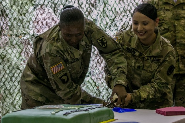 Command Sgt. Maj. Jennifer J. Callicutt, (left), the senior enlisted advisor for 53rd Movement Control Battalion, 7th Transportation Brigade, Fort Eustis, Virginia, and Sgt. Stephanie Millan, (right), assigned to Headquarters and Headquarters Detachment, 53rd MCB, hold a ceremonial saber as they cut into a cake, concluding the noncommissioned officer induction ceremony May 11, 2018 in Poznan, Poland. The NCO induction ceremony is a celebration of the newly promoted joining the ranks of a professional noncommissioned officer corps and emphasizes and builds on the pride shared as members of an elite corps. (U.S. Army photo by Spc. Dustin D. Biven / 22nd Mobile Public Affairs Detachment)