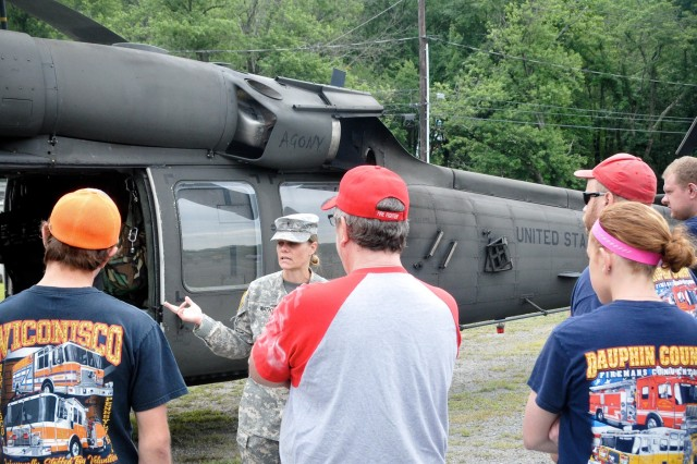 U.S. Army Chief Warrant Officer 3 Danielle Watkins, safety officer for the 628th Aviation Support Battalion, briefs civilian first responders from Dauphin and Schuylkill counties on the UH-60 Black Hawk helicopter at Wiconisco, Pa., July 21, 2018.