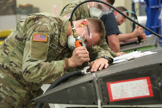 Spc. Samuel Andrychowski, 1109th Theater Aviation Maintenance Group,  Connecticut Army National Guard, performs a composite repair at the U.S. Army Aviation and Missile Research, Development and Engineering Center's Prototype Integration Facility during a composites repair course on July 10.