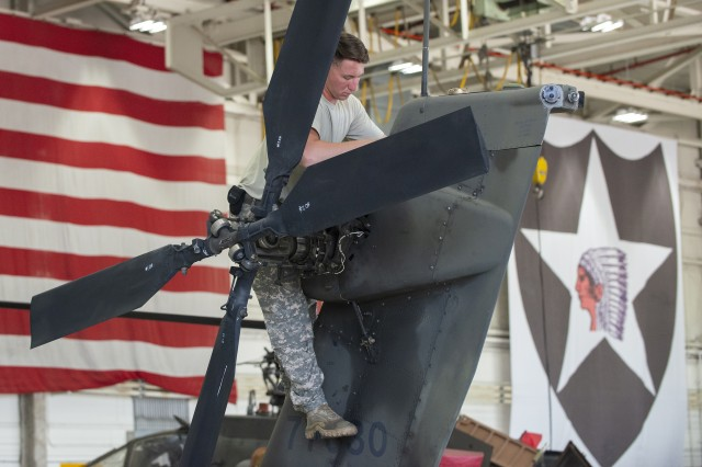 Pfc. Ben Yandell, assigned to the 2nd Combat Aviation Brigade, performs maintenance on an Apache helicopter inside a hangar at Camp Humphreys, South Korea, May 31, 2018.