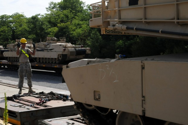 Soldiers with the Ohio Army National Guard's 1st Battalion, 145th Armored Regiment ground guides a M88 Hercules tank off a train bed at Fort Knox, Kentucky July 19, 2018. The vehicles will be kept and maintained at the Kentucky National Guard's Maneuver Area Training Equipment Site (MATES) facility. (U.S. Army National Guard photo by staff Sgt. Benjamin Crane)
