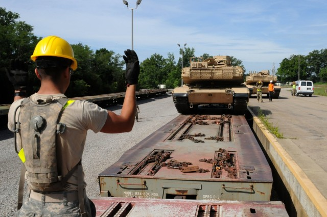 A Soldier with the Ohio Army National Guard's 1st Battalion, 145th Armored Regiment ground guides a M1A1 Abrams tank off a train bed at Fort Knox, Kentucky July 19, 2018. The vehicles will be kept and maintained at the Kentucky National Guard's Maneuver Area Training Equipment Site (MATES) facility. (U.S. Army National Guard photo by staff Sgt. Benjamin Crane)