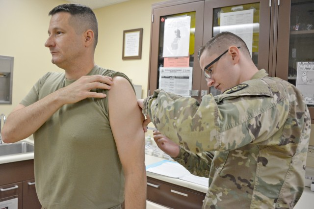The Tripler Army Medical Center Allergy & Immunizations Clinic Noncommissioned Officer in Charge, Sgt. Christopher Hutchins, right, administers the Measles, Mumps, Rubella vaccine to Sgt. 1st Class Chad Williams, left, TAMC Medical Specialties Clinic 2 NCOIC, Jan. 31, 2018, at the TAMC Allergy & Immunizations Clinic.