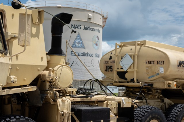 An M1088 Tractor Truck and fuel tanker belonging to the 418th Transportation Company stage at Naval Air Station Jacksonville during the Quartermaster Liquid Logistics Exercise on July 18, 2018.