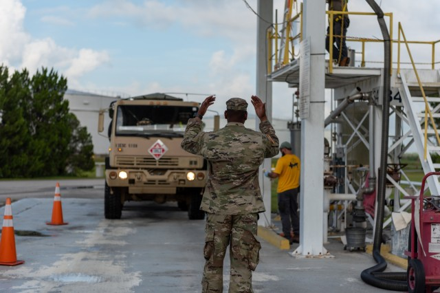 A Soldier from the 61st Quartermaster Battalion guides an M1088 Tractor Truck and fuel tanker into place to pick up fuel at the Defense Fuel Support Point in North Jacksonville for delivery to Naval Air Station Jacksonville during the Quartermaster Liquid Logistics Exercise on July 18, 2018.