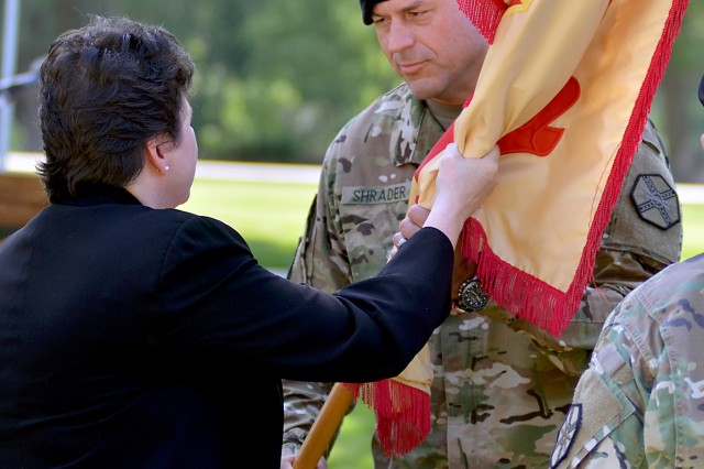 Col. Stephen Shrader receives the Fort Riley Garrison guidon from Brenda Lee McCullough, director, Installation Command-Readiness, July 13 during a change of command ceremony at Ware Parade Field. Shrader replaced Col. John D. Lawrence as garrison commander.