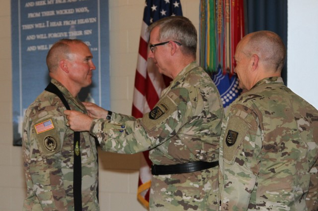 NETCOM Command Chaplains changed hands during a Change of Stole ceremony at Kino Chapel, Fort Huachuca, Ariz., July 23.  Passing the Stole from Chaplain (Col.) Richard Garvey (right) to the new command chaplain, Chaplain (Lt. Col.) Will Horton (left) is NETCOM Commanding General, Maj. Gen. John Baker.