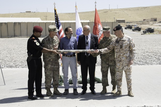 Representatives of each partner on the Mosul Dam stabilization project hold a core sample representing the mutual goal of stabilization. From left, Col. Muntadar, Iraq; Col. Mike Farrell, outgoing Commander, Mosul Dam Task Force; Mr. Miconi, Project Manager,Trevi; Mr. Riyadh, Iraq Ministry of Water Resources; Col. Philip Secrist, Commander, Mosul Dam Task Force; and Col. Settesoldi, Commander, Task Force Presidium.