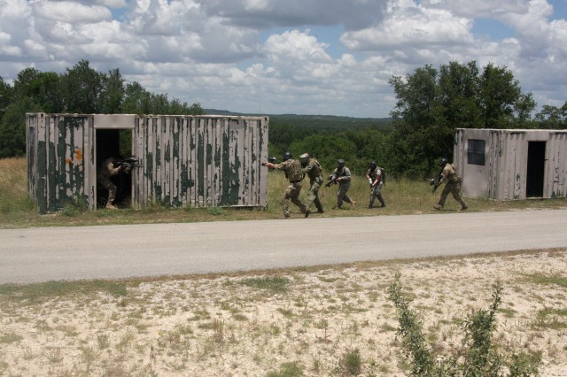 Special Forces conduct a raid on the village of a high value individual on the range area of Camp Bullis during the 2018 Joint Emergency Medical Exercise held in mid-June. The Special Forces practiced close quarter combat as they searched for the enemy. Simulated casualties from the fire fight were then evacuated to a forward medical team.