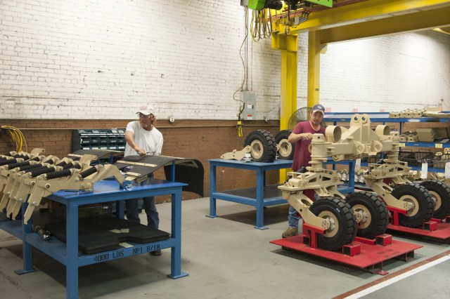 Kenny Norton, left, and Phillip Abernathy assemble mine rollers in the Turret Systems #2/Artillery Branch at Anniston Army Depot. The organization repainted and reorganized work areas to ensure compliance with proper color coding and improve work flow.