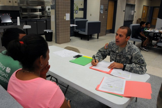 U.S. Army Reserve Soldier Sgt. Hector Blanco, a combat specialist, completes in-processing with local residents waiting for medical services at Betty Harwell Middle School in Edinburg, Texas. Approximately 50 U.S. Army Reserve Soldiers assigned to the 7235th Medical Support Unit out of Orlando, Texas, worked in partnership with the Texas A&M Colonias program June 16-27 to provide medical care to Hidalgo County's underserved colonia population. Services provided by military personnel are done through the Department of Defense's Innovative Readiness Training, a civil-military program that builds mutually beneficial partnerships between U.S. communities and the DoD. The missions selected meet training & readiness requirements for Army Reserve service members while integrating them as a joint and whole-of-society team to serve our American citizens.