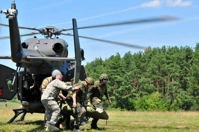 U.S. Army Capt. Morris Duffy (left front), a flight surgeon assigned to 1st Battalion, 112th Aviation Regiment, North Dakota Army National Guard, helps train German Bundeswehr Reserve soldiers with medical air evacuation training at the Joint Multinational Readiness Center's Hohenfels training area, Hohenfels, Germany, July 19, 2018. Nebraska and North Dakota Army National Guard Soldiers are participating in multinational interoperability training, which enhances the working relationship between the U.S. and the host nation.