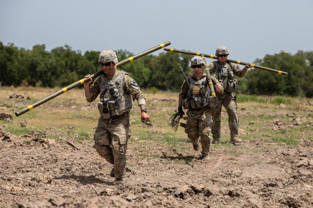 Army combat engineers with the 1st Cavalry Division's 2nd Armored Brigade Combat Team move to emplace Bangalore torpedoes on an obstacle during breaching operations training at Fort Hood, Texas, July 17, 2018.