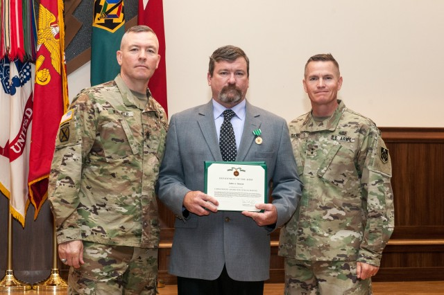 James Benton stands with Command Sgt. Maj. Trevor Walker, U.S. Army Engineer School, and Maj. Gen. Kent Savre, MSCoE and Fort Leonard Wood commanding general, after receiving the Commander's Award for Civilian Service for Meritorious Achievement for winning Civilian Instructor of the Year for the U.S. Army Chemical, Biological, Radiological and Nuclear School. Benton also won first place in the TRADOC level competition.