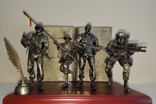"The Colombian army took great care in crafting the physical design of the Benn and Soto Award. The book in the back is an actual doctrine manual dipped in metal. Front left is a quill pen and ink to represent the writing process. The soldiers depicted have historical significance to the Colombian army. Second from left is a soldier carrying a lance who represents the revolutionary war period and those ""Lanceros"" who fought the Spaniards. To his left is a soldier from the Korean War time frame representing those who fought side-by-side with the United States Army. The soldier in the beret represents those soldiers who fought against the FARC (Revolutionary Armed Forces of Colombia) for the last 52 years. Last is the modern soldier, poised to spring forward, in a representation of interoperability and the ability to support the interests of good."