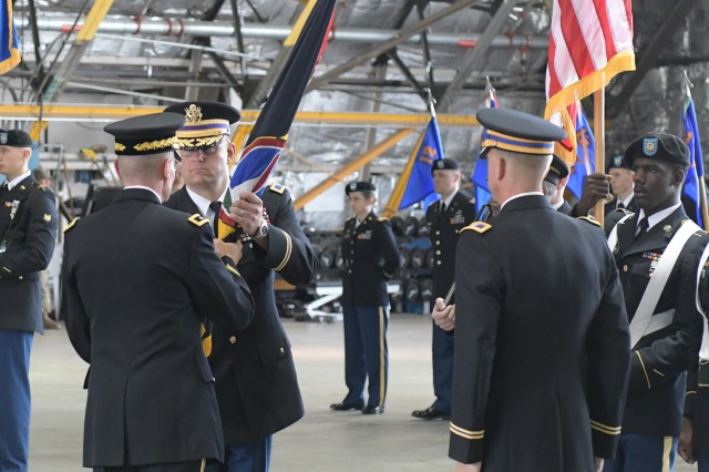 Col. Mark G. Kappelmann (second left), recieves the U.S. Army Aviation Brigade guidon from Maj. Gen. Michael L. Howard, Joint Force Headquarters-National Capital Region/U.S. Army Military District of Washington, commanding general during a Change of Command and Change of Responsiblity Ceremony held at the Lakota Hanger, Davison Army Air Field, Fort Belvoir, Virginia, July 25. (U.S. Army photo by Cory Hancock, JFHQ-NCR/MDW Public Affairs)