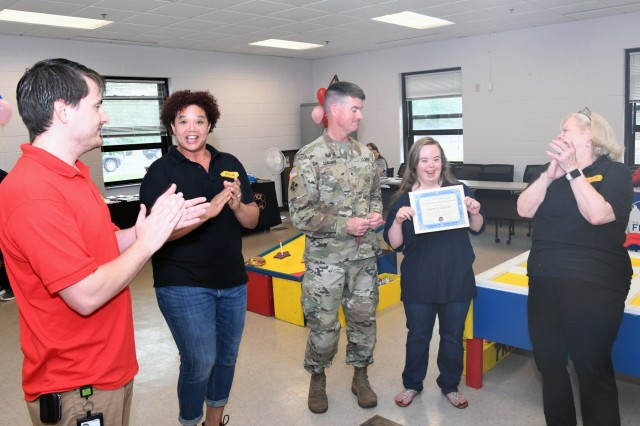 Brig. Gen. Patrick Donahoe, 10th Mountain Division (LI) deputy commanding general, presents Sierra Coons with a certificate of achievement July 25 for having accumulated more than 2,000 hours of volunteer service at Army Community Service during the ACS birthday celebration. (Photo by Mike Strasser, Fort Drum Garrison Public Affairs)