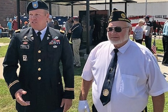 Army Materiel Command's Maj. Mike Harrell and Gold Star father David Muhr greet residents of Coon Rapids, Iowa, after a dedication ceremony honoring Muhr's son, Shawn, and others who died while serving the nation.