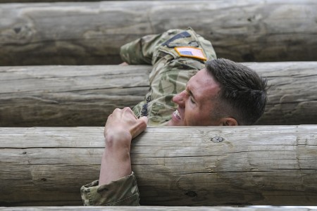 A Soldier representing 7th Infantry Division, attempts the over and under obstacle during the second day of their Best Warrior Competition, May 15, 2018, at Joint Base Lewis-McChord, Wash. The course consisted of various physically exhausting obstacles and the soldiers task was to complete the course as quickly as possible.