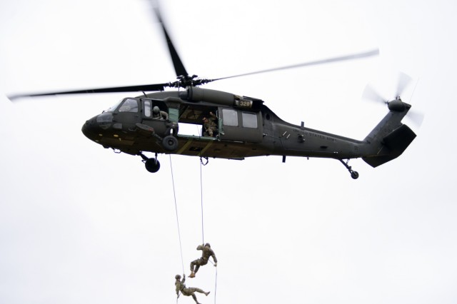 An Oregon Army National Guard HH-60M Black Hawk helicopter hovers 90-feet above the ground while two National Guard Soldiers rappel from the aircraft during an aircraft command and control test, June 13, 2018, at Camp Rilea near Warrenton, Oregon. Soldiers were tested in groups of three, with two rappelling Soldiers and one graded Rappel Master student, under the guidance of Warrior Training Center instructors from Fort Benning, Georgia. Students must score 100-percent in order to successfully graduate from the the weeklong course.
