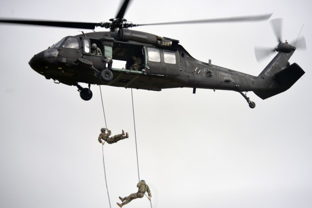 Two Army National Guard Soldiers rappel nearly 90-feet down from an Oregon Army National Guard HH-60M Black Hawk helicopter during the aircraft command and control portion of the Rappel Master Course, June 13, 2018, at Camp Rilea near Warrenton, Oregon. Soldiers must successfully send rappelling Soldiers out of the aircraft and score 100-percent in order to pass the test.