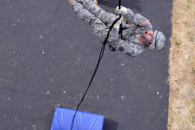 Washington Army National Guard Sgt. Darin A. Munhall descends from a 60-foot rappel tower, one of his three open-side rappels required within 24-hours of a helicopter rappel, June 12, 2018, at Camp Rilea, near Warrenton, Oregon. Soldiers were given an aircraft control and command test the following day, which demonstrates their ability to successfully send multiple rappelling Soldiers out of a rotary-wing aircraft  at approximately 90-feet above the ground.