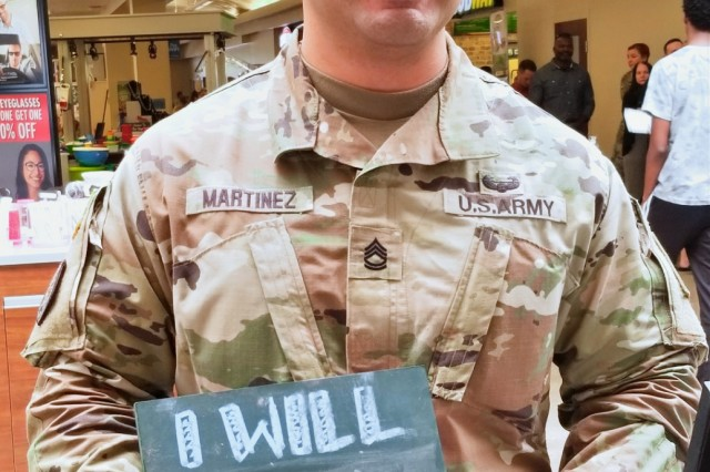 """4th Cavalry Multi-Functional Training Brigade S2, Sgt. 1st Class Andrew Martinez, poses with his """"I will"""" pledge, July 23, at the Fort Knox Post Exchange. The """"I Will"""" Campaign is a campaign that allows personnel to write on chalk boards how they will support survivors of sexual assault. (U.S. Army photo by Sgt. 1st Class Jillian Webber / 4th Cav. MFTB)"""