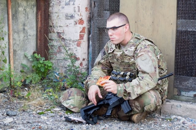 A Soldier enjoys a Meal, Ready-to-Eat pizza developed by scientists in the Combat Feeding Directorate at the Natick Soldier Research, Development and Engineering Center. CFD used a combination of technologies involving water activity, pH levels, and innovative packaging to create a shelf-stable pizza.