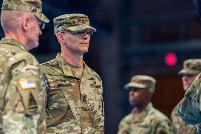 Command Sgt. Maj. Richard A. Woodring (center), stand after assuming responsibility for the Joint Force Headquarters-National Capital Region and the U.S. Army Military District of Washington, during a change of responsibility ceremony June 12, 2018. The ceremony was hosted by Maj. Gen. Michael L. Howard, commanding general, JFHQ-NCR/MDW, in Conmy Hall on Joint Base Myer-Henderson Hall, Va. (U.S. Army photos by Sgt. Nicholas T. Holmes)
