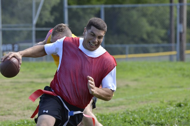 A quarterback tries to elude a defender during a flag football game Aug. 16, 2017, during Victory Week 2017. (Sgt. Elizabeth Jones, 19th Public Affairs Detachment)