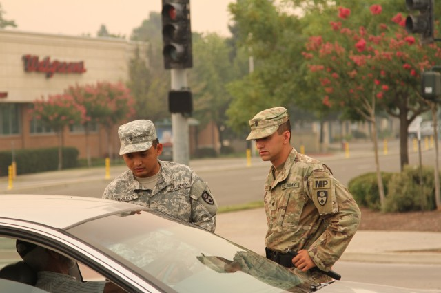 U.S. Army Spcs. Rodavlas Manliclic and Mailo Gonzalez of the 870th Military Police Company, 185th Military Police Battalion, 49th Military Police Brigade, California Army National Guard, control a traffic point at an active intersection July 29, 2018 where the Carr Fire passed through and continued to expand.