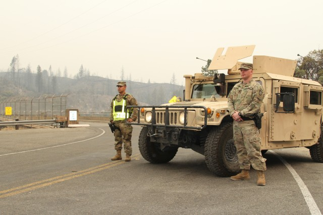 Sgt. Jesus Valencia and Spc. Cameron Hodges of the California Army National Guard's 270th Military Police Company, 185th Military Police Battalion, 49th Military Police Brigade, secure a checkpoint July 29, 2018 at the Keswick Dam in Redding, Calif., shortly after the Carr Fire passed through the area.