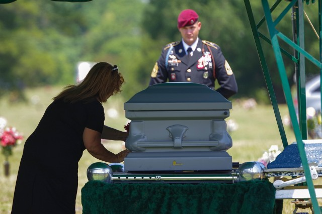 A family member of retired 1st Sgt. Harold Eatman, left, places a flower on his casket at Sharon Memorial Park in Charlotte, North Carolina on July 11 as 1st Sgt. James Miller, right, of Company, B, 2nd Battalion, 505th Parachute Infantry Regiment looks on.  Eatman was a member of the 505th PIR during World War II, making combat jumps into Sicily, Salerno, Normandy and Holland.  Eatman passed away earlier in July at the age of 102.