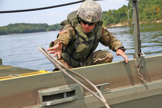 Spc. Tyler Browning with the 2061st Multi-Role Bridge Company unties a rope from a interior bridge bay during River Assault 2018 on the Arkansas River near Fort Smith, Ark., July 25, 2018. The Kentucky Guardsmen participated with Army Reserve, active duty Army and Marine Corps units for the annual engineer exercise.