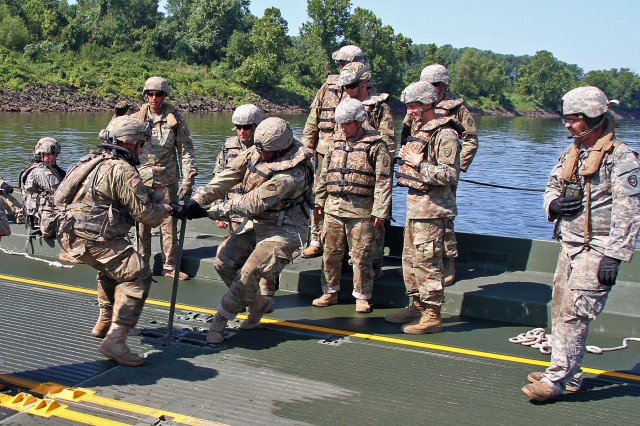 Soldiers with the Kentucky National Guard's 2061st Multi-Role Bridge Company and the U.S. Army Reserves' 739th MRBC work to connect their bridge assemblies during River Assault 2018 on the Arkansas River near Fort Smith, Ark., July 25, 2018. The two units worked together to form a large portion of an improvised ribbon bridge during the annual engineer exercise.