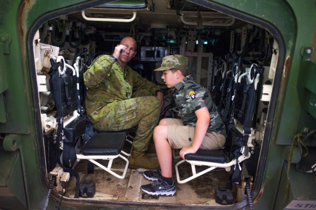 Australian army Sgt. 1st Class Ewan B. Jack, left, instructor, talks combat vehicles with 9-year-old Eli Wilson. Wilson visited locations throughout Fort Benning, Georgia, July 26, 2018.