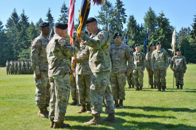 """Lt. Col. Matt Rasmussen, the outgoing commander of 1st Battalion, 17th Infantry Regiment, hands the unit guide-on to Col. Jay Miseli, the commander of the 2nd Stryker Brigade Combat Team, during a change of command ceremony at Watkins Field at Joint Base Lewis-McChord, Washington, July 26, 2018.  """"You know what, I'm pretty lucky, and our country and our Army is pretty lucky too because of the Buffalos you see before you today; these are Soldiers and leaders who understand their purpose,"""" said  Rasmussen."""