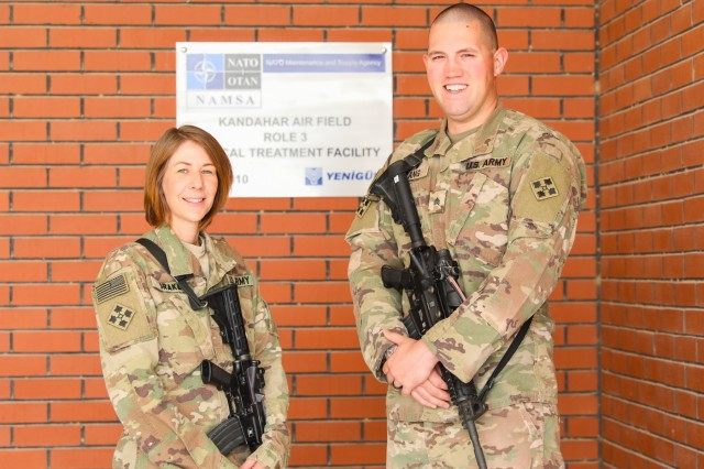Capt. Kelly Drake and Sgt. Kert Lang, behavioral health team for the 2nd Infantry Brigade Combat Team, 4th Infantry Division, pose for a photo, July 27, 2018, in front of Role III Hospital in Kandahar Airfield, Afghanistan. Drake and Lang provided classes for service members throughout the airfield to help mitigate stressors that could arise. (U.S. Army photo by Staff Sgt. Neysa Canfield/ TAAC-South Public Affairs)