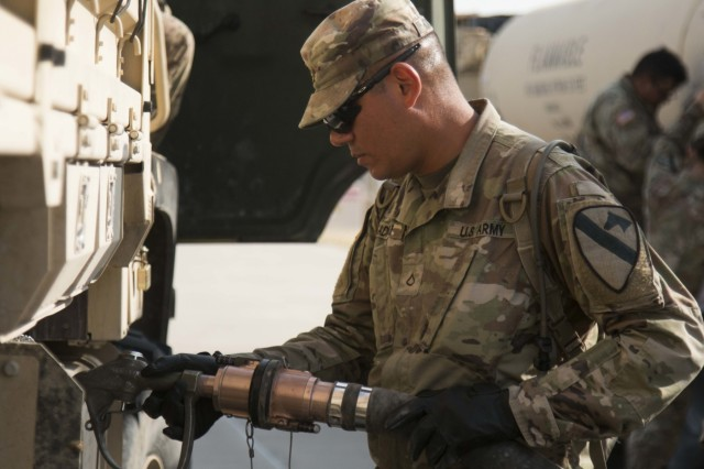 Pvt. 1st Class Yasir Kadhum, an 88M (truck driver) assists in fueling vehicles during a driver's training class, July 26, 2018.