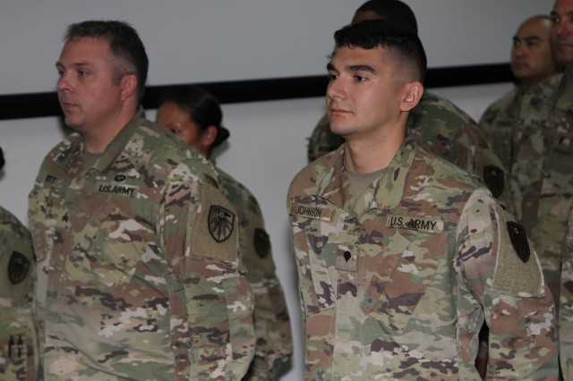 Battle captains for the 2d Regional Cyber Center, Sgt. Michael Witt, left, and Spc. Matthew Johnson, stand in formation awaiting the start of a patching ceremony.  The 2RCC officially changed their shoulder sleeve insignia patch to the U.S. Army Cyber Command patch during a ceremony on the 2RCC watch floor, July 25, Fort Huachuca, Ariz.