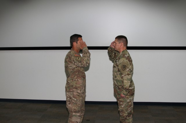 Lt. Col. Joseph Gilbert, right, 2d Regional Cyber Center director, reports to Brig. Gen. Richard Angle, deputy commanding general for Operations, U.S. Army Cyber Command, at the start of a patching ceremony for the 2RCC.  The 2RCC officially changed their shoulder sleeve insignia patch to the ARCYBER patch during a ceremony on the 2RCC watch floor, July 25, Fort Huachuca, Ariz.