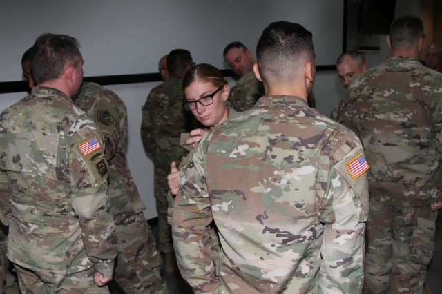 Spc. April Lemon, a battle captain for the 2d Regional Cyber Center, places the U.S. Army Cyber Command shoulder patch on a fellow Soldier during a patching ceremony on the 2RCC watch floor, July 25, Fort Huachuca, Ariz.