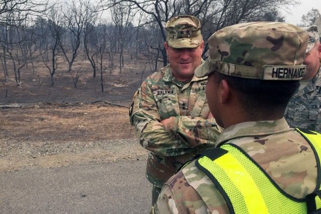 U.S. Army Maj. Gen. David S. Baldwin, left, adjutant general of the California National Guard, meets Spc. Jesse Hernandez of the 270th Military Police Company, 85th Military Police Battalion, 49th Military Police Brigade, July 30 at a Keswick Dam Road traffic point burned up by the Carr Fire in Redding, California.