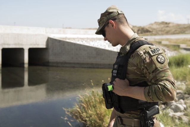Military Police Investigator Joshua Higgins, 156th Military Police Law and Order Detachment, West Virginia Army National Guard, performs random anti-terrorism measure by checking culverts for tampering on Bagram Airfield, Afghanistan, July 28, 2018. Members of the 156th Military Police Law and Order Det. are deployed to both Bagram and Kandahar Airfields where they perform law and order operations for both installations.