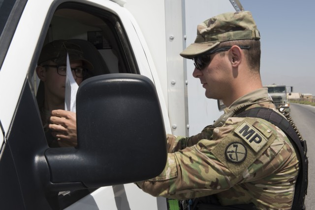 Military Police Investigator Joshua Higgins, 156th Military Police Law and Order Detachment, West Virginia Army National Guard, performs vehicle registration and driver's documentation as part of a random anti-terrorism measures on Bagram Airfield, Afghanistan, July 28, 2018. Members of the 156th Military Police Law and Order Det. are deployed to both Bagram and Kandahar Airfields where they perform law and order operations for both installations.